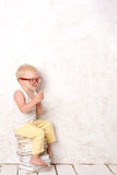 Boy sits on white painted books Royalty Free Stock Photography