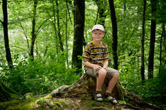 A boy sits in the wild woods Stock Photos