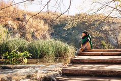 Boy sits on wooden bridge over the mountain lake Royalty Free Stock Photography