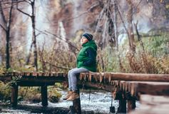 Boy sits omn wooden bridge over river in mountain autumn forest. Boy sits on wooden bridge over river in mountain autumn forest Royalty Free Stock Photo