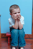 Boy sitting. Little Boy sitting on a stool with hands on face stock images