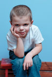 Boy sitting. Little Boy sitting on a stool with hands on face royalty free stock photography