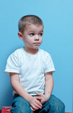 Boy sitting. Little Boy sitting on a stool with hands on face stock photos