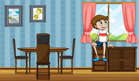 A boy sitting above the cabinet near the window Stock Images