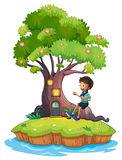 A boy sitting above the roots of a tree amazed by the treehouse Stock Images