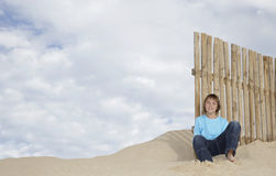 Boy Sitting Against Wooden Fence On Sandy Beach Royalty Free Stock Photo