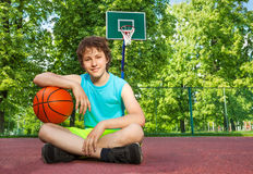 Boy sitting alone with elbow on the ball Stock Images