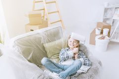 Easy home improvement. Boy sitting on an armchair covered with a protective plastic sheet and holding a paint roller, home improvement and renovation concept stock photo