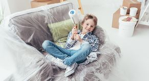 Easy home improvement. Boy sitting on an armchair covered with a protective plastic sheet and holding a paint roller, home improvement and renovation concept royalty free stock images