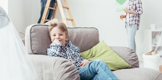 Home improvement. Boy sitting on an armchair while his parents are painting the room, home improvement concept Royalty Free Stock Images