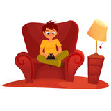 Boy sitting on the armchair and playing tablet Royalty Free Stock Photography
