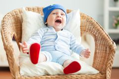 Boy is sitting on armchair Stock Image