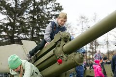 The boy is sitting on the artillery gun, which stand near the museum of the Victory Memorial during the celebration of Victory Day. KRASNOYARSK, RF - May 9, 2018 stock image