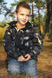 Boy sitting in autumn pine forest on earth. Stock Photography