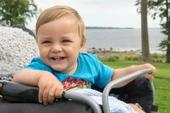 The boy is sitting in the baby carriage and laughs Royalty Free Stock Photos