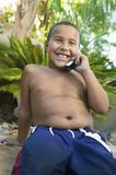 Boy sitting in back yard Using Cell Phone front view Royalty Free Stock Photos