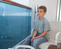 Boy sitting on balcony of ship Royalty Free Stock Photo