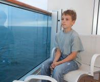 Boy sitting on balcony of ship. Little boy sitting on balcony of ship with view on sea Royalty Free Stock Photo
