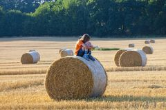 Boy Sitting on a Bale of Hay Boy Sitting on a Bale of Hay in Su Stock Image