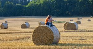 Boy Sitting on a Bale of Hay in Summer Stock Photos
