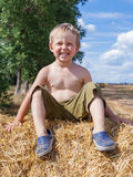 Boy sitting on bale straw Royalty Free Stock Photography
