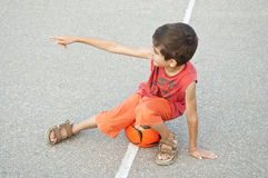 Boy sitting on ball poiting Stock Photos