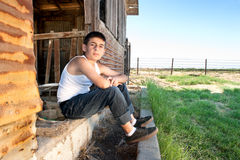 Boy sitting in barn Stock Images