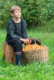 Boy sitting with basket full of chanterelles Stock Photography