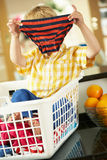 Boy Sitting In Basket Sorting Laundry. On Kitchen Counter Royalty Free Stock Images