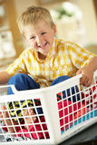 Boy Sitting In Basket Sorting Laundry Royalty Free Stock Image