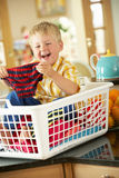 Boy Sitting In Basket Sorting Laundry. On Kitchen Counter Royalty Free Stock Photo