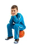 Boy sitting on basketball Stock Photo