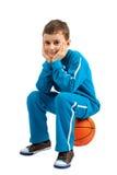 Boy sitting on basketball Stock Photo