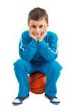 Boy sitting on basketball Stock Image