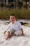 Boy sitting on the beach Stock Photo