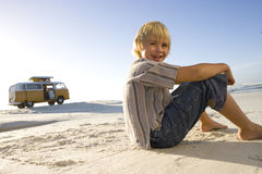 Boy (6-8) sitting on beach, camper van in background, smiling, portrait, low angle view Stock Photo