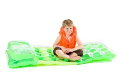 Boy sitting on beach mattress. Little boy sitting on green inflatable mattress, wearing orange life vest. Isolated on white stock image
