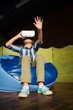 Boy sitting on bean bag and using virtual reality headset. At home Stock Photography