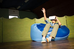 Boy sitting on bean bag and using virtual reality headset. At home Stock Photo