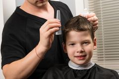 The boy is sitting in the beauty salon, he is made with hair styling stock photography