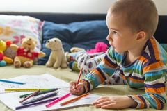 Little child boy drawing with color pencils. Children`s creativity. Boy sitting on the bed and drawing on coloring book with color pencils Royalty Free Stock Image