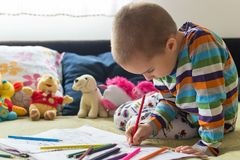 Little child boy drawing with color pencils. Children`s creativity. Boy sitting on the bed and drawing on coloring book with color pencils Stock Images