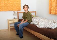 Boy sitting on bed Royalty Free Stock Images