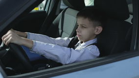The boy is sitting behind the steering wheel of the car and dreams to drive like an adult. stock video footage