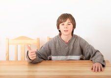 Boy sitting behind wooden table Royalty Free Stock Photos