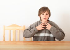Boy sitting behind wooden table Royalty Free Stock Photo