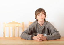 Boy sitting behind wooden table Stock Images