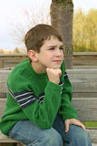 Boy Sitting on Bench. A young boy sitting on a bench Stock Photo