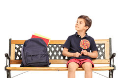 Boy sitting on a bench and holding lollipop Stock Photo