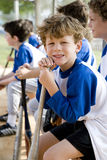 Boy sitting on bench with little league baseball team Royalty Free Stock Photography